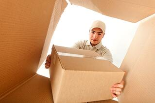 Delivery man holding a package inside a cardboard box